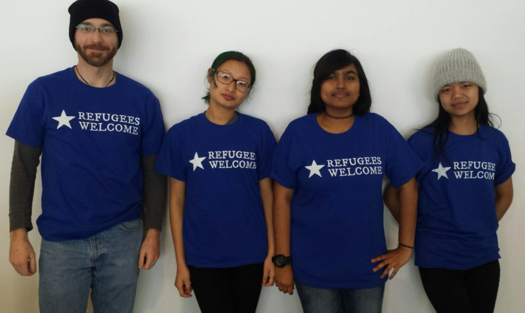 "Four models wearing the ""Refugees Welcome"" t-shirt graphic, designed for the Worcester Refugee Assistance Project (Worcester, Massachussetts, USA). Desiger: Ben Young Landis/Creative Externalities. The photo shows the front of the t-shirt, which is a royal blue. The graphic reads: ""Refugees Welcome"" in white ink, with a white star graphic."