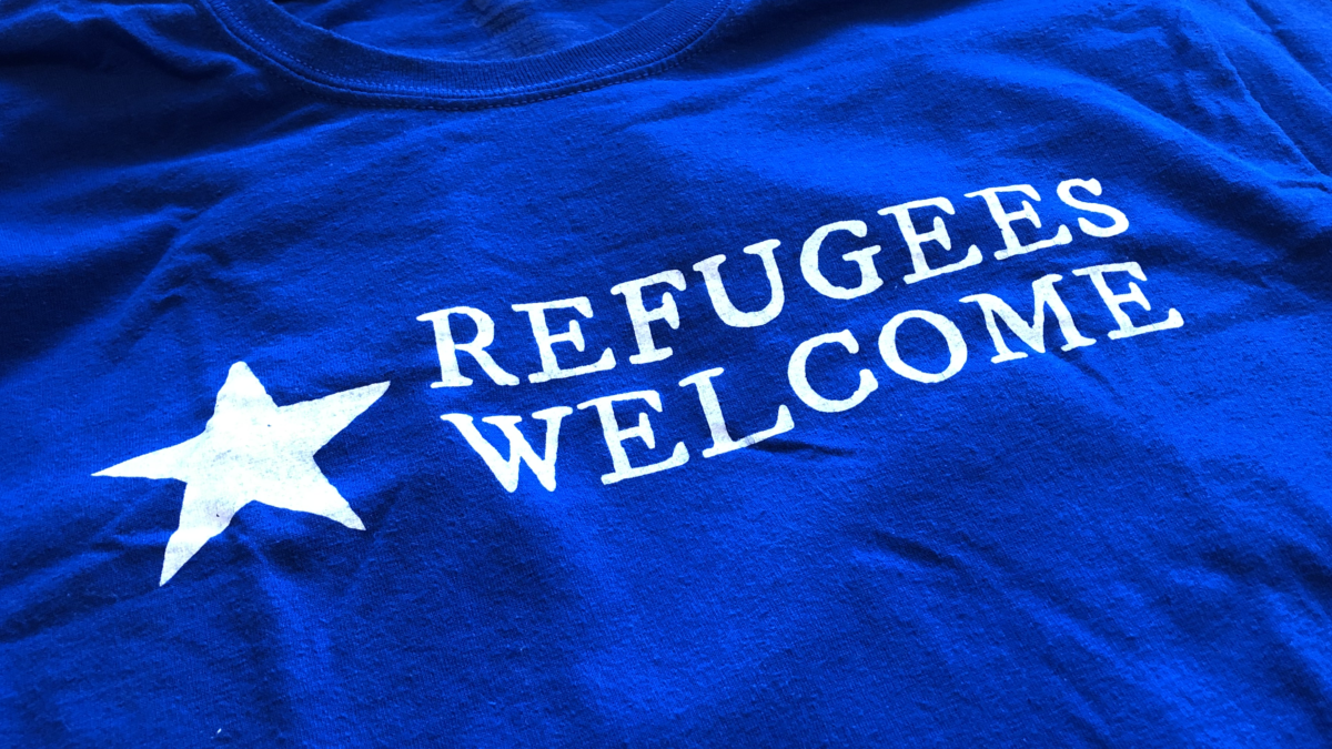 """Refugees Welcome"" t-shirt graphic, designed for the Worcester Refugee Assistance Project (Worcester, Massachussetts, USA). Desiger: Ben Young Landis/Creative Externalities. The photo shows the front of the t-shirt, which is a royal blue. The graphic reads: ""Refugees Welcome"" in white ink, with a white star graphic."