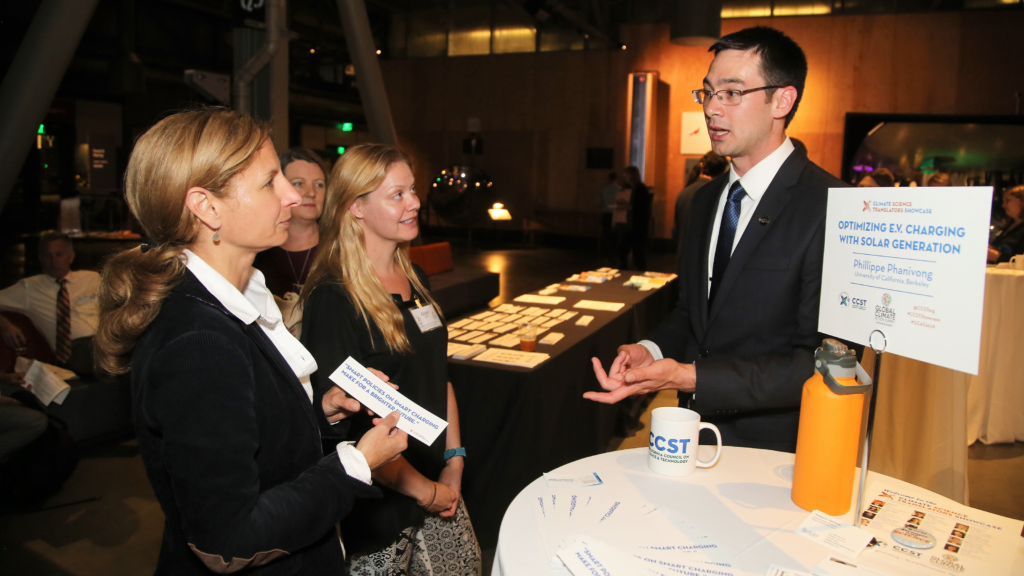 "UC Berkeley doctoral student Phillippe Phanivong explains his research on optimizing solar energy grid production with electric vehicle charging times to guests at the OPR ""Celebration of Science and Education"" reception.  The California Council on Science and Technology (CCST) hosted the CCST Climate Science Translators Showcase on Tuesday, September 11, 2018 at the Exploratorium as an Affiliate Event of the historic Global Climate Action Summit in San Francisco — held during the ""Celebration of Science and Education"" reception hosted by the Governor's Office of Planning and Research (OPR), CCST, the Gordon and Betty Moore Foundation, CalEPA, and Ten Strands. The #CCSTShowcase recruited and trained 12 graduate students and postdocs from California universities and research institutions to communicate their climate-related research to policy leaders, staff, and other Summit delegates."