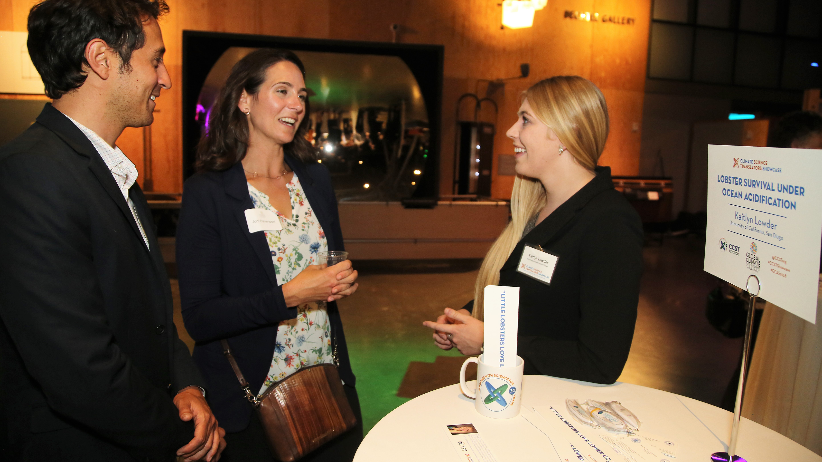 """UC San Diego Scripps Institution of Oceanography doctoral student Kaitlyn Lowder explains her research on ocean acidification and juvenile crustaceans at the CCST Climate Science Translators Showcase.  The California Council on Science and Technology (CCST) hosted the CCST Climate Science Translators Showcase on Tuesday, September 11, 2018 at the Exploratorium as an Affiliate Event of the historic Global Climate Action Summit in San Francisco — held during the """"Celebration of Science and Education"""" reception hosted by the Governor's Office of Planning and Research (OPR), CCST, the Gordon and Betty Moore Foundation, CalEPA, and Ten Strands. The #CCSTShowcase recruited and trained 12 graduate students and postdocs from California universities and research institutions to communicate their climate-related research to policy leaders, staff, and other Summit delegates."""