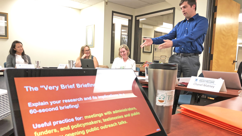 "A scene from a ""Connecting with Your Audience"" Workshop taught by Ben Young Landis for the CCST Science & Technology Policy Fellowship. Here, 2019 CCST Science Fellow Jared Ferguson gestures during his practice briefing in front of colleagues. Jared is wearing a French blue dress shirt and gray trousers. A laptop screen shows the text ""The Very Brief Briefing""."
