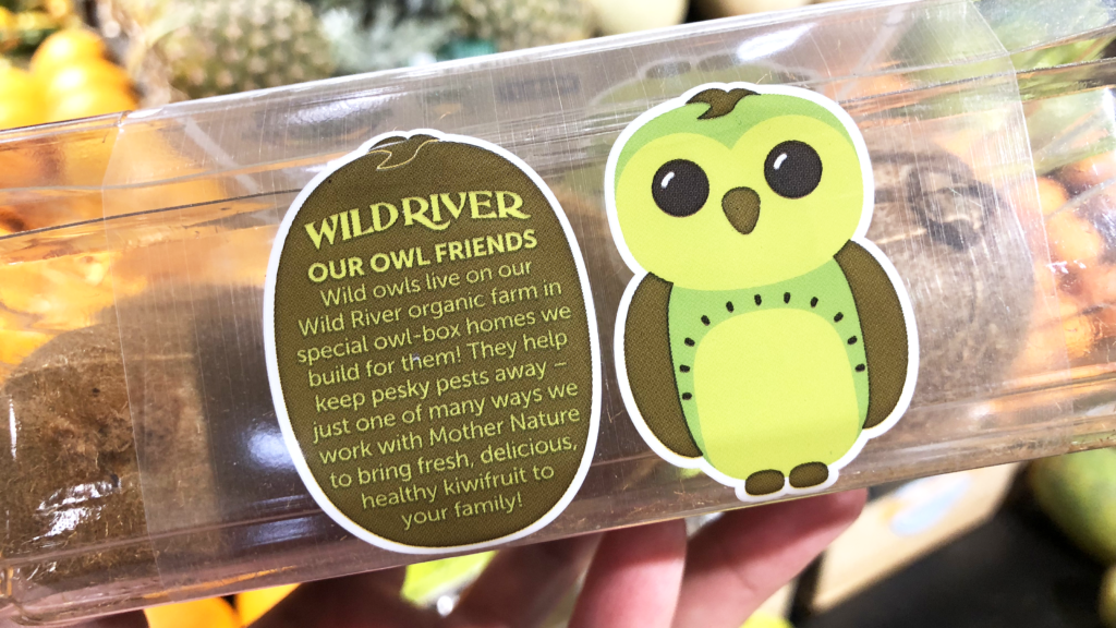 Our Owl Friends and associated kiwi owl logos are trademarks of Wild River Marketing Inc. Designed by Ben Young Landis and Guy Rogers. The photo shows the front side of a Wild River plastic clamshell container for kiwifruit. Next to a green kiwi owl, the text reads: Our Owl Friends: Wild owls live on our Wild River organic farm in special owl-box homes we build for them! They help keep pesky pests away — just one of many ways we work with Mother Nature to bring fresh, delicious kiwifruit to your family!