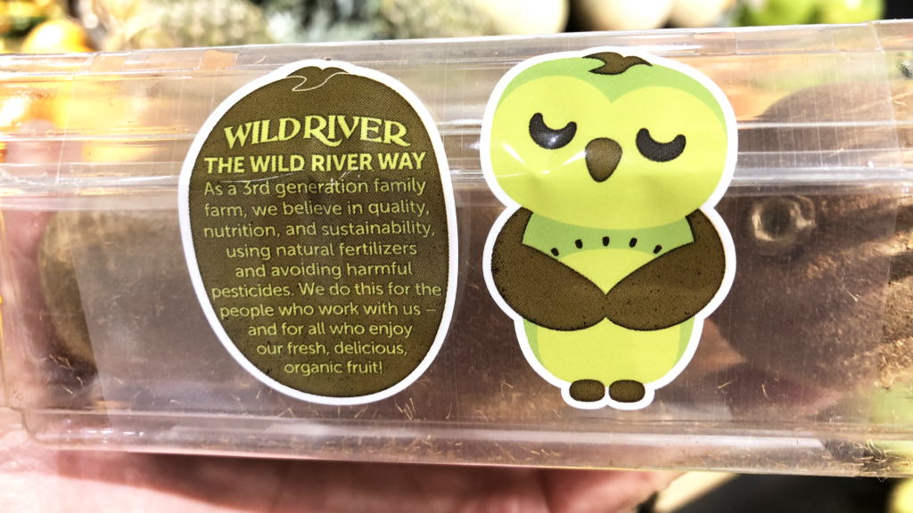 Our Owl Friends and associated kiwi owl logos are trademarks of Wild River Marketing Inc. Designed by Ben Young Landis and Guy Rogers. The photo shows the back side of a Wild River plastic clamshell container for kiwifruit. Next to a green kiwi owl, the text reads: The Wild River Way: As a third generation family farm, we believe in quality, nutrition, and sustainability, using natural fertilizers and avoiding harmful pesticides. We do this for the people who work with us — and for all who enjoy our fresh, delicious, organic fruit!