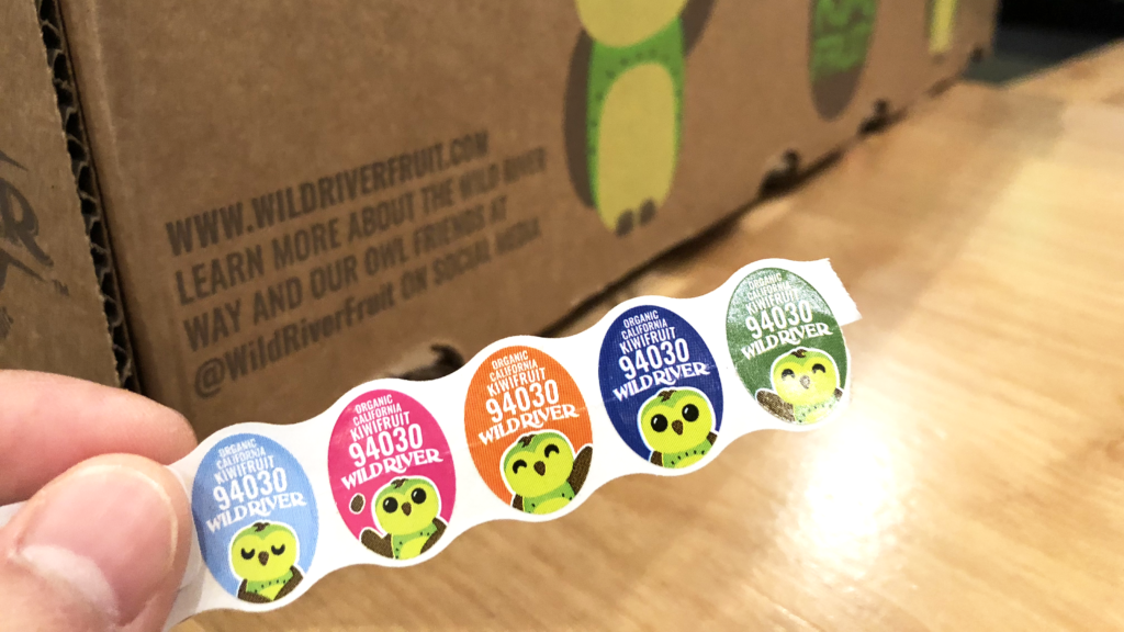 Our Owl Friends and associated kiwi owl logos are trademarks of Wild River Marketing Inc. Designed by Ben Young Landis and Guy Rogers. The photo shows a series of P L U stickers created for Wild River kiwifruit. Each oval sticker has a green kiwi owl in a pose (respectivul, playful, waving, standing, waving), against blue, pink, orange, dark blue, and green backgrounds. The stickers read: Organic California Kiwifruit 94030 Wild River.