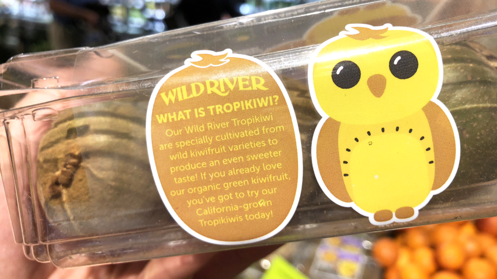Our Owl Friends and associated kiwi owl logos are trademarks of Wild River Marketing Inc. Designed by Ben Young Landis and Guy Rogers. The photo shows the front side of a Wild River plastic clamshell container for kiwifruit. Next to a old kiwi owl, the text reads: What is Tropikiwi? Our Wild River Tropikiwi are specially cultivated from wild kiwifruit varieties to produce an even sweeter taste! If you already love our organic green kiwifruit, you've got to try our California-grown Tropikiwis today!
